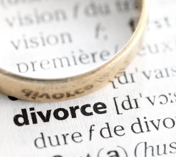 Divorce term highlighted in macro from dictionary book, with a wedding ring.