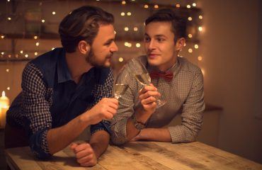 Loving gay couple having romantic date, drinking champagne. Domestic kitchen. Handsome caucasian man looking at each other. Evening scene lit by candle and string lights.
