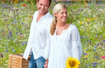 Couple on picnic in countryside walking in field of wild summer flowers
