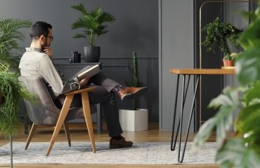 Modern man reading book while sitting in grey armchair in trendy interior with plants