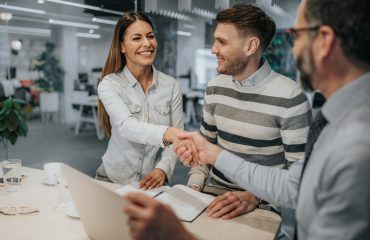 Happy couple came to an agreement with their insurance agent in the office. Focus is on woman shaking hands with an agent.