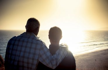 Gay couple looking at sunset