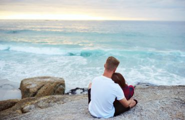 Shot of a happy young couple relaxing on a rock together at the beach