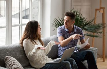 Young couple arguing about high domestic bills to pay with laptop and documents, unhappy family having conflict disagreement discussing unpaid debt or money problems sitting together on sofa at home