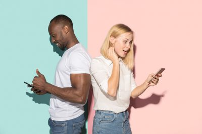 couple of students taking mobile phones. The surprised caucasian girl and her african boyfriend posing at studio . Communication and relationship concept. Date coaching