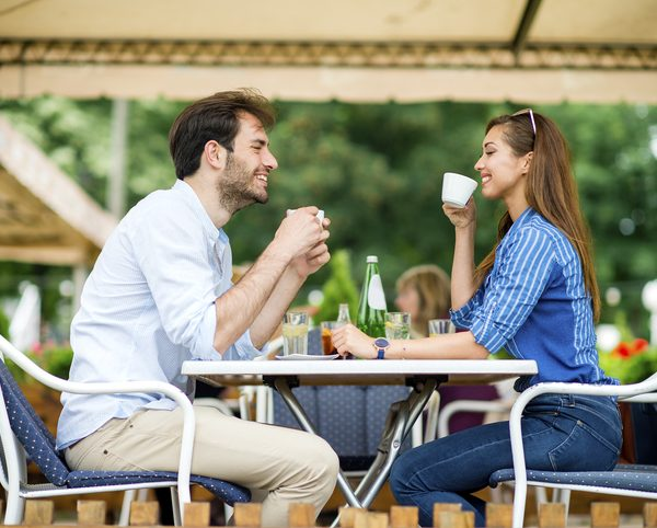 Loving couple at coffee house having coffee and chatting