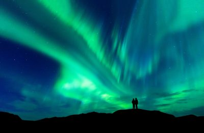 Aurora borealis lights with silhouette love romantic couple on the