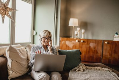 Mature woman is in her modern apartment using a laptop to create her online dating profile