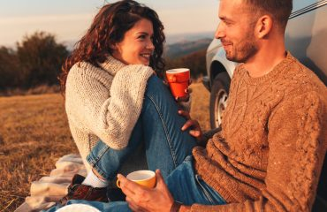Beautiful young couple dating in their thirties and enjoying picnic time on the sunset. They drinking tea and sitting in a meadow leaning against a old fashioned car.