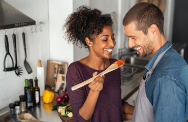 Young couple tasting tomato sauce while cooking in the kitchen. Cheerful man and smiling woman holding spatula in hand ready to taste red sauce. Multiethnic couple cooking together at home. No arguments.