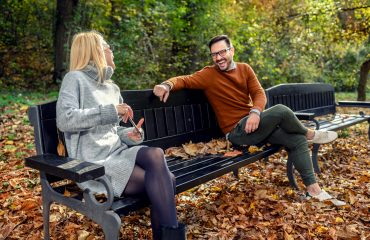 Woman and man in social distancing flirting sitting on a park bench for an outdoor date