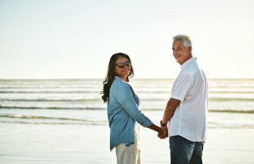 Portrait of a happy senior couple spending a day at the beach, looking back on the past