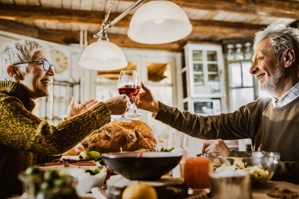 Happy mature couple toasting with wine while having Thanksgiving meal in dining room. to say thank you