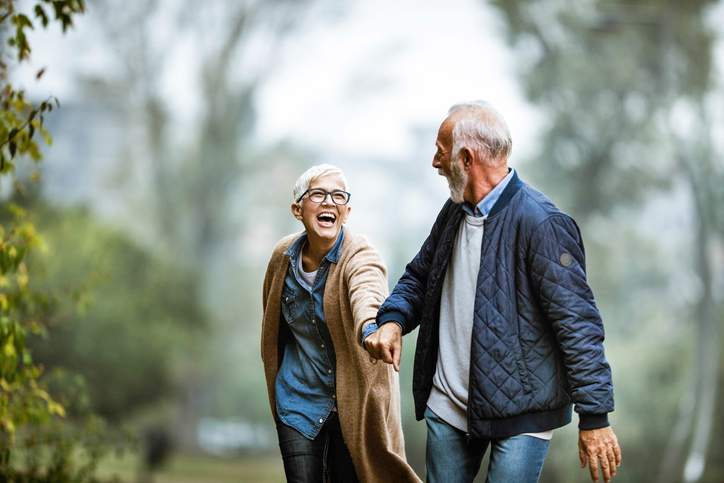 Cheerful senior couple having fun in the park. Focus is on woman. Copy space., dating