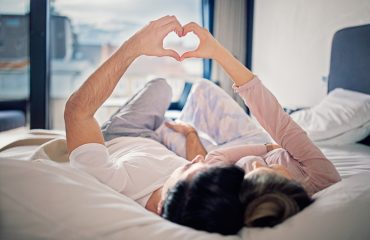 Couple is lying on the bed and making heart with their hands, unconscious bias