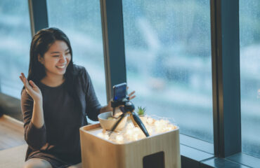 an asian chinese teenager girl vlogging in her room eating apple using her smart phone during raining day smiling date
