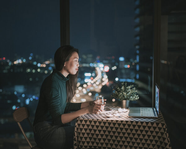 an asian chinese beautiful young lady having dessert in her apartment during magic hour, dusk and talking to her boyfriend thru internet using her laptop to online dating
