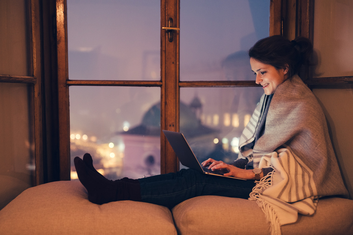 Young woman sitting at the window sill during a positive virtual date.