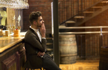 A young man is dressed smarty at a bar waiting, he looks fed up as if he has been stood up on a date. One hand is on his face and the other is holding his smart phone.