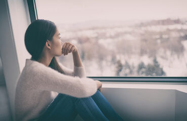 Woman looking out of window with relationship anxiety